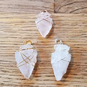 ENDAST 1 KVAR! Pilspets-format hängsmycke av rosenkvarts. Cirka 3-4 cm långt.   Går att få i färgerna: silver, guld och rose. Färg och form på kristallen kan variera lite då det är en naturlig sten, och formen är huggen för hand.   Skickas i vadderat kuvert via postnord.