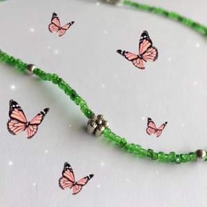 Halsband med seed beads i grönt & har en liten silvrig blomma🌸🌷Gjort med nylontråd och har en förlängning på 3 cm. Säljer för 40kr + 12kr i frakt!