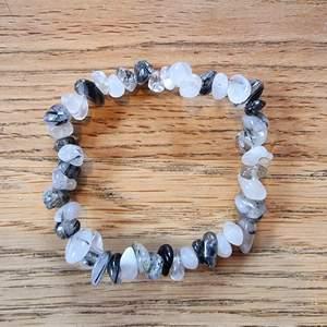 Armband med kristallpärlor av turmalin i kvarts. Chipsformade stenar trädda på elastisk tråd. Ca 16 cm omkrets. Skickas i vadderat kuvert via postnord.
