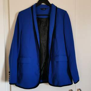 An electrifying cobolt blue blazer with black velvet detailes around the collar and buttons. Don't remember where I bought it but Heidi Klum has designed It. Never worn.