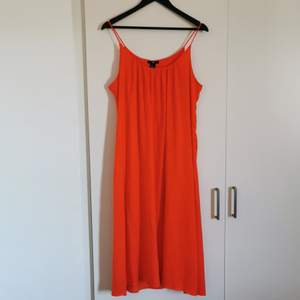 A dress in the brightest of orange color. Long dress, like under the knees. Has a built in under dress. Satin feel. Never worn. Spaghetti straps. Hot for the summer 😍