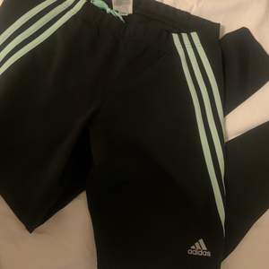 Adidas träningstights, använda få gånger. Tighta hela benen. Mintgröna sträck som går från midjan till halva låret. Högmidjade. Storlek M