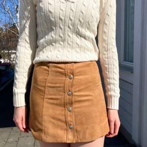 En fin kjol i mocka material som passar perfekt till hösten. Den har en fin färg och är lite fodrad på insidan. Storleken är 32. Den är i nyskick eftersom den knappt blivit använd och jag säljer den för att den dels är för lite för liten för mig och för att det inte riktigt är min stil.