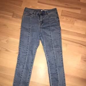 Supersnygga jeans från Nakd. Har en söm i mitten av benen och en slit längst ner. Dessa jeans är slutsålda för länge sen.