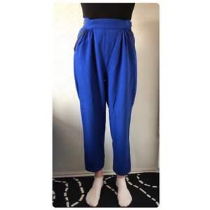 """Blåa mjuka byxor med svarta """"skinn"""" detaljer vid fickan från modeskaparen Gunilla Ponténs klädkollektion."""