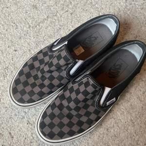 """Ett par """"Classic Slip-on"""" Vans med mörkt checkerboard mönster. Köpta i våras men bara använda ett fåtal gånger, så väldigt bra skick⭐️ 400kr inkl. frakt🌷"""