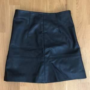Svart fakeläder kjol med gömd dragkedja bak. Storlek 34, säljer för att den är för liten, annat tyg på insidan vilket är svalare, snygga sömmar