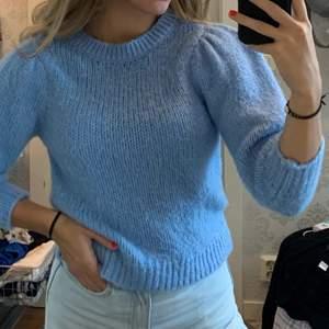 En blå stickad tröja med trekvarts armar. Använd ca en gång