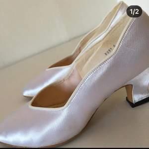 Sidenklädda skor storlek 37,5 i fint skick. Använda en gång, litet märke på sidan. Vita, glansiga , passar till den vita dräkten jag också säljer. 100kr