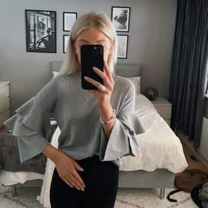 Finstickad grå tröja från BikBok i storlek xs. Tröjan är tunt stickad med volanger på armarna. Passar storlek XS/S beroende på hur man vill att den ska sitta