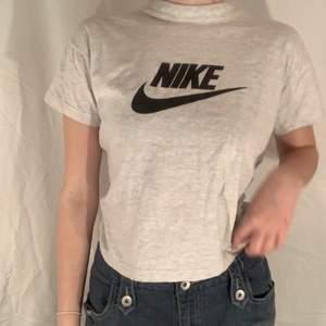 Ljusgrå / vit T-shirt med svart tryck från Nike. Fint skick.