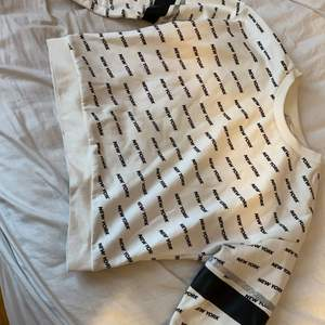 En fin lång armad tröja med svarta och glitter streck på armen