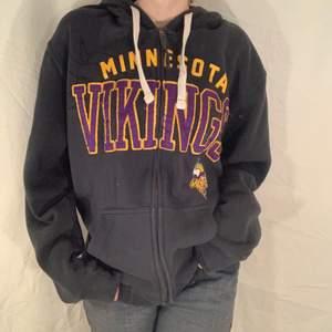 Mörkgrå hoodie med lila och gult tryck som läser Minnesota Vikings från NFL. Fint skick.