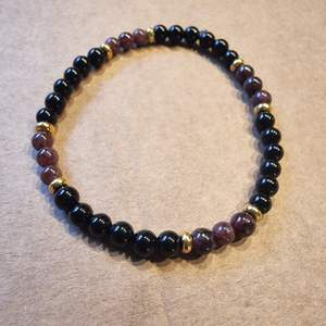 Armband med 4 mm små kristallpärlor av onyx och granat, samt guldfärgade pärlor. Rundslipade stenar trädda på elastisk tråd. Ca 16 cm omkrets.  Skickas i vadderat kuvert via postnord.