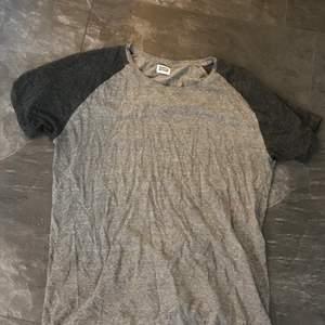 En ljusgrå tshirt med mörkgråa armar från Weekday i storlek XL.
