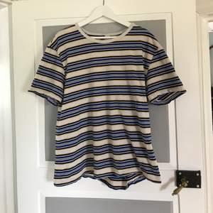 En jättesnygg vit t-shirt med ränder i gul, blå och svart. Använd en del och är i lite krassligt skick då sömmar har börjat gå upp:( Köpt på H&M i storlek L. säljer pga den inte används. 30kr + frakt.