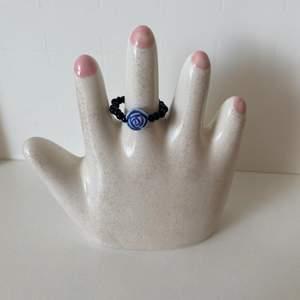 Handgjord ring som är svart med en blå ros i mitten 🥀