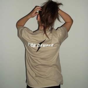Nu säljer vi de sista exklusiva och populära exemplaren av vårt UFs-shirt kollektion! Dessa t-shirts är ekologiska, GOTS-certifierade och SJUKT sköna! De storlekar i beige som finns kvar är M, denna passform är unisex och riktigt trendigt oversized🖤 Modellen bär storlek M på bilderna och är en XS-S normalt🖤Budskapet på ryggen är uppenbart och står för kampen mot cancer🖤