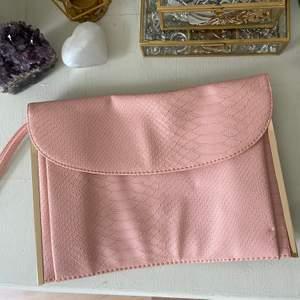Baby rosa clutch väska från Primark, med ormmönster & guld detaljer. Handledsrem men ingen kedja medföljer. ALDRIG använd så i utmärkt skick!