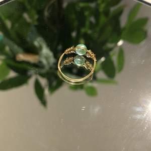 En hemmagjord ring med en turkos pärla och rostfri ståltråd i färgen guld. Fin att ha som vardagsring men ocksånär man vill vara lite finklädd.