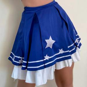 Indigo blue with stars sown onto it. Stretchy waist and a two layered skirt.