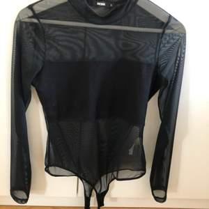En svart mesh body från bik bok. Storlek s. Enkel och passar till fest. Som en bandå fram till brösten och bara mesh på ryggen. Köparen står för frakten.