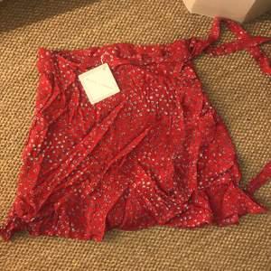 """Aldrig använd. Röd med vitblåa detaljer. Kort. Wrap skirt. Märke """"house of sienna"""", tror dock jag beställde den från princess polly. Storlek 10 Amerikansk storlek!"""