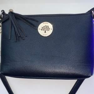 Säljer denna snygga svarta handväskan med guld detaljer! Märket är mulberry men den är inte äkta! Köptes för 450 kr och jag säljer den nu för 150 kr + frakt. Endast använd ett fåtal gånger! Vill man ha måtten på den kan man skriva privat så ska jag mäta åt er 🥰