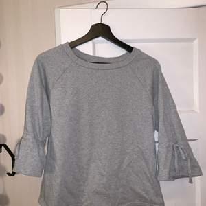 Supersöt grå tröja i storlek S! Söta knytditaljer på armarna! Nästan aldrig använd! Skriv vid frågor eller om ni vill ha fler bilder!