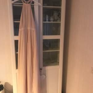 Ljusrosa balklänning med slits där fram från Nelly eve i storlek 36. Använd endast en gång och i bra skick.