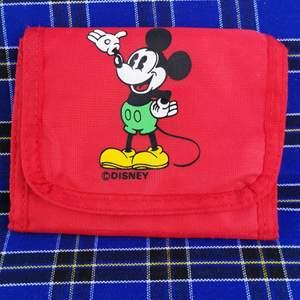 Så söt Mickey-plånbok köpt secondhand. Är i fint skick förutom färg som skavts bort från dragkedjehänget. Mäter på längden cirka 13 cm och bredden cirka 10 cm. Frakt för denna ligger på 11 kr, samfraktar gärna 👍😊
