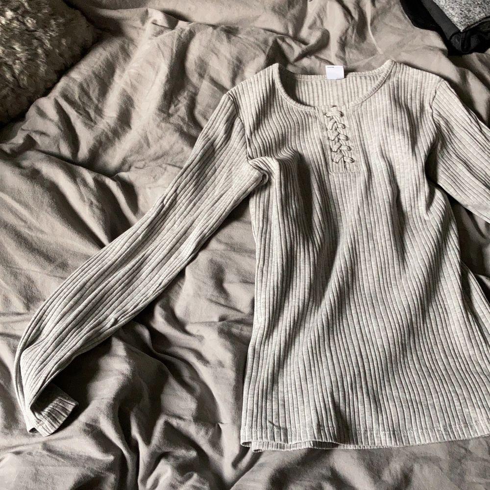 Grå randig tröja med en fläta i mitten💓köpare står för frakt. Tröjor & Koftor.