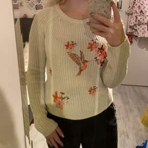 Sekler en stickad tröja med blommor och en fågel på. Storlek s. Den är lite smånopprig, därav priset