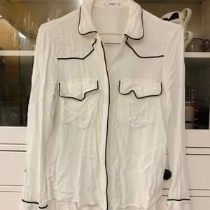 Skjorta med svarta detaljer. Skrynklig på bild då jag ej har strukit den. Köpt på Mango använd några fåtal gånger. Säljer pga bror av användning.