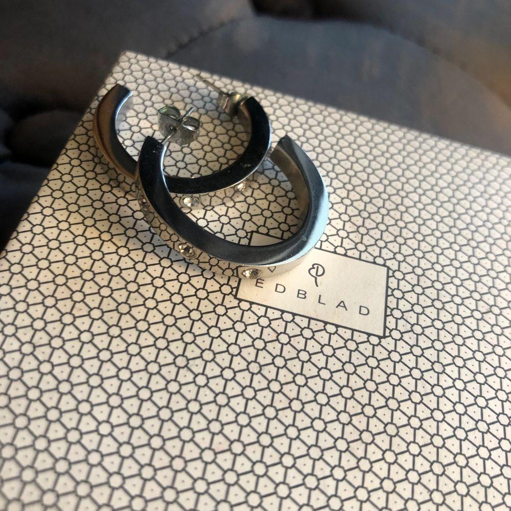 Snygga tjockare ringar/hoops i silver med små stenar från Edblad. I nyskick, originalask ingår. 99 kr + frakt. Accessoarer.