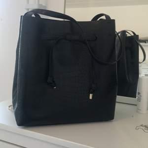 """Denna super fina väska från hm. Svart med croc mönster. Använd några gånger men fortfarande super bra skick. Man kan dra åt den vid """"snörena"""" för att stänga. Priset är inte med frakt."""