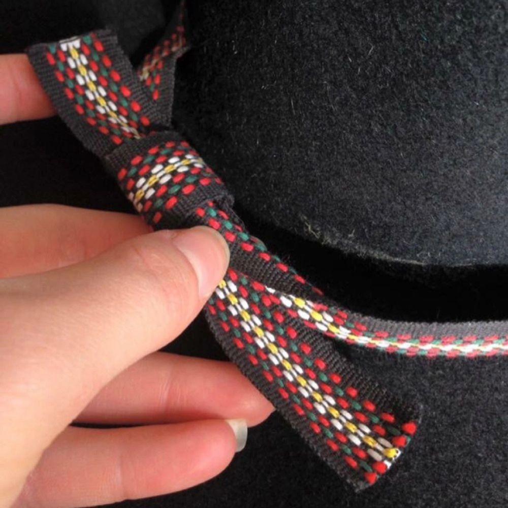 Svart hatt i ull prydd med ett snyggt band. Innermått 55 cm. Brettet mäter 36 cm på bredden och 39 cm på längden. Enda skavanken är att bandet släppt lite baktill, men det fixas lätt med lite lim! Porto 98 kr tillkommer (Shenker), alternativt upphämtning i Gävle.. Accessoarer.
