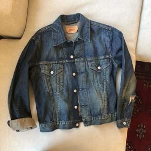 Jeansjacka från LEVI's, köp för ett antal år sen, använd enstaka gånger och därför säljer jag den nu. Den är i nyskick. Inköpspris 900 kr.   Ganska liten i storleken, och jag har själv för det mesta M i andra jackor och tröjor, skulle säga att den motsvarar herrars kostymstorlek 48.