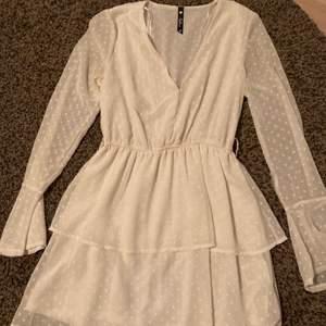 Vit klänning med volanger. Använd endast vid 1 tillfälle, på studenten. Lite genomskinligt material vid armarna.