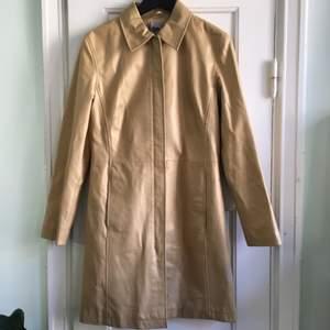 Fin beige, glansig kappa, 90tal, fina dragkedjor, använd en gång, från ett gammalt lager så aldrig använd innan jag köpte den. Äkta läder. Jag är en 36a men det är på håret att den passar, tror 34 är bättre, men funkar på en 36a också.  Nice leather jacket vintage 90's retro