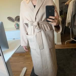Jättefin beige/sandfärgad, lång kappa från Zara med bälte i midjan som ger en fin siluett! Innehåller 44% ull. Är i storleken S, men är lite oversized så skulle säga att den passar allt från S-L beroende på hur man vill att den ska sitta. Köparen står för frakten 🧚🏼♂️