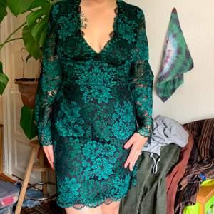 Fin klänning från H&M med mättade gröna/grönblå färger och svart. Urringningen är superfin och ärmarna är bara i spets. Är i nyskick då den aldrig blivit använd. Frakt inkluderat i priset!