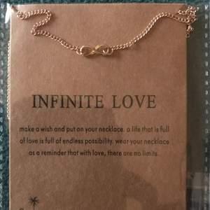 Guld pläterat halsband med symbolen för infinitiv love  samt en text till .