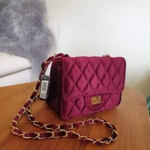 Vinröd väska från Montini i velvet-material. Oanvänd med lappen kvar. Mått: 17 x 13 x 7 🌟 nypris 298 kr. Finns vid Gärdet, köparen står annars för frakt.
