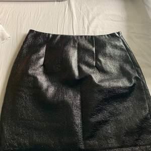Säljer en svart kjol med coolt material från Nelly. 70kr+frakt.