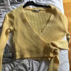 Gul fin tröja, i nyskick. Använts fåtal gånger. Knyte i sidan, v-ringad. Croppad och ribbad. Köpare betalar frakt.