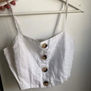 Croppat linne med knappar från Gina tricot🤍🤍 Använd en gång så är som ny! Ganska litet i storleken, passar på mig som har XS/34 i toppar.