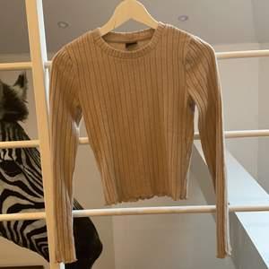 Långärmad tröja från Gina tricot i bra skick. Mjukt material och beige färg. Är ganska kort croppad med fina detaljer i ärmar och längst ned, och passar både XS och S även om storleken är XS.