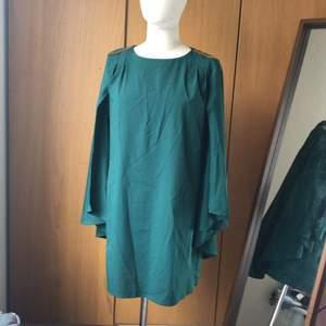 Supersmickrande cape klänning. Passar storlek 36-38. (Klänningen är grönare än på bild och inte petrolblå) Använd endast 1 gång. Helt fin och felfri. Kan fraktas eller mötas upp i Stockhomsområdet.