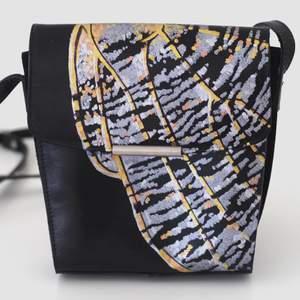 Superfin väska i läder! Köpt second hand och målad med färger i metallic som fäster på läder. Är lite sliten på bandet, men syns knappt! 20 x 19 cm